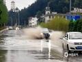 车辆通过积水路段溅起水花。(图/石奎)