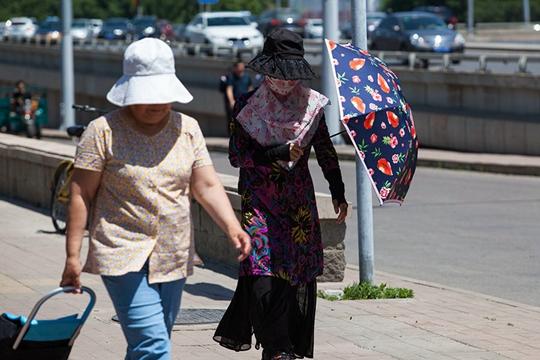 北京迎今年首个高温日 阳光火辣民众出行遮阳忙