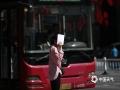 22日下午2点,河北石家庄裕华路,户外气温38.1℃,骄阳似火,市民用随手携带的纸遮阳。(图/刘琦)