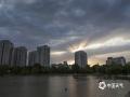 """中国天气网讯 5月26日,北京出现雷雨天气,雨后傍晚时分,一束束阳光透过云层洒向大地,如""""佛光普照""""。这种在西方被称为""""上帝之光""""的现象,学名叫做""""丁达尔现象""""或者""""丁达尔效应"""",是由于雾气或是大气中的灰尘,散射阳光而形成。 (图/王晓)"""