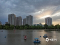 """5月26日,北京出现雷雨天气,雨后傍晚时分,一束束阳光透过云层洒向大地,如""""佛光普照""""。这种在西方被称为""""上帝之光""""的现象,学名叫做""""丁达尔现象""""或者""""丁达尔效应"""",是由于雾气或是大气中的灰尘,散射阳光而形成。 (图/王晓)"""
