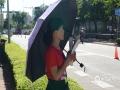 中国天气网讯 今日(7日)上午,海口实验中学门外,天气晴间多云,温度34℃。图为考生家长在炎热的阳光下打伞等待考生。(文/图 董立就 林俊汝)