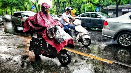 湖南吉首:小满至雨水来 市民早高峰冒雨出行