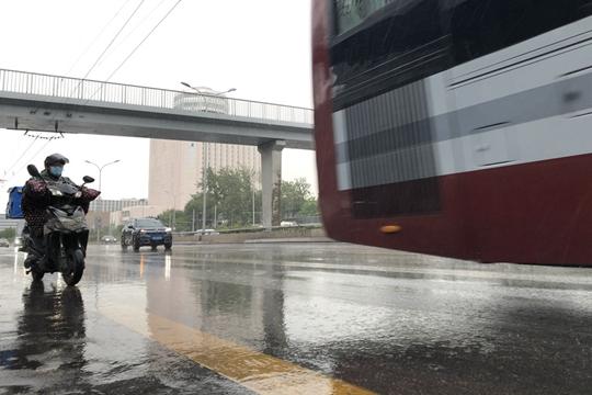 北京再迎雷阵雨 天空阴沉地面湿滑