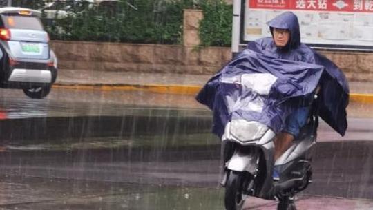 河南郑州突遭大雨 街头路人忙赶路