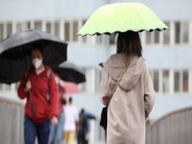 北京雨水飘落秋意浓 街头市民换厚装撑伞出行