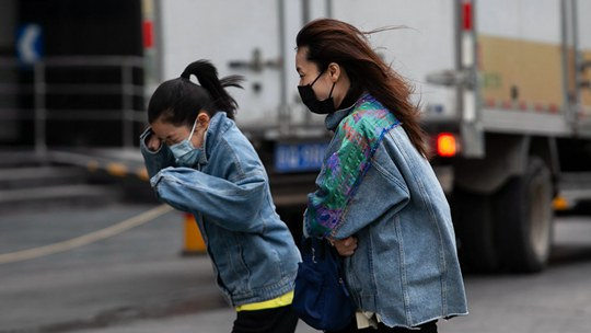 北京冷风呼呼吹 街头行人厚装出行泥点车排长队