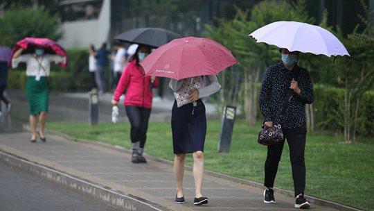 北京雷声隆隆雨水洒落 街头行人步履匆匆