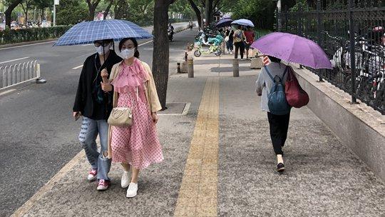 北京西部小雨洒落 市民撑伞出行