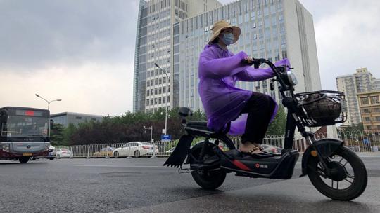 北京阴云起雨滴落 街头行人携雨具出行