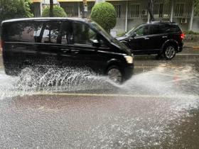 北京降雨来袭 行人撑伞出行车辆溅起水花