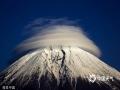 2015年1月19日消息(具体拍摄时间不详),日本富士山,在晴朗的一天,神奇的云层在富士山山顶形成了一个奇特的环形形状,这是由于潮湿气流在高纬度遇到了例如山脉或者建筑这样的障碍物,阻断了气流的流通,随着空气中水分的凝结,下风侧形成了这样的奇特景观。(chinafotopress/版权图片 来源视觉中国)