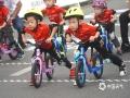 中国天气网广西站讯 10月22日,2019年环广西公路自行车世界巡回赛进入最后一日的争夺战,车手们雨中竞速争夺赛事总冠军。在今日的桂林城市赛段中,来自全球18支顶级职业车队的车手们从桂林市中心广场出发,一路疾驰168.3公里,最终回到桂林市中心广场。尽管阴雨绵绵,当天比赛仍受到桂林市民和游客的热烈欢迎,车手们所到之处均赢得了赛道沿途观众的热情欢呼和鼓励。图为小自行车爱好者热场。(文/胡静 图/杨艳丽)