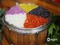 """中国天气网广西站讯 3月26日,正值壮族""""三月三"""",民间有制作五色糯米饭的习俗。壮族儿女在""""三月三""""采摘枫叶、红蓝草、黄饭花和紫蕃藤等植物原料,将糯米染色,做成色泽鲜艳、清香诱人的五色糯米饭庆祝传统节日。图为:制作好的""""五色糯米饭""""。(图/吴永才 文/涂燕清)"""