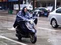 图为14日早上,钦州市民在雨中骑车出行。(图/李斌喜)