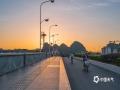 中国天气网讯  秋季北风渐烈,10月22日桂林迎来了朗朗晴天,朝霞将天空染成了橘色,霞光柔和的照耀着大地,清晨漓江解放桥上是匆匆的赶路人,桥下也不乏晨泳人,人景两相宜,清晨漓江更添了几分妩媚。(文/郁海蓉 图/曾海科)