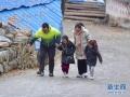 1月8日,受强冷空气影响,融水县杆洞乡高寒山区出现冰冻,部分道路结冰,小学生在老师、家长和驻村工作队员的护送下到校上课。图为,当天在杆洞乡党鸠村乌英苗寨,驻村工作队员郑昌昊护送小学生去学校。新华社记者 黄孝邦 摄