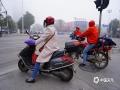 图为22日早晨,钦州市民在雾中骑车。(图/李斌喜)