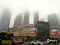 """中国天气网讯 近日广西接连被阴雨包围。今晨,受偏南暖湿气流影响,广西中部多地遭遇大雾袭击,局地能见度不足50米。图为:南宁昨天和今天连遭大雾影响,高楼在白茫茫的雾气笼罩中若隐若现仿佛坠入""""仙境""""。(图/老曾 文/郁海蓉)"""