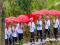 """6月13日,广西龙脊迎来了一年一度的梳秧节,恰逢端午假期,雨后天晴的龙脊梯田景区游客如织,格外热闹,图为打着红伞跟在""""秧母娘娘""""后面的红瑶姑娘。(文/张雅昕 图/莫家勋)"""