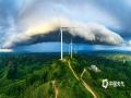 """9月5日傍晚,广西横州霞义山上空,骤雨、夕阳、彩虹共同上演一场""""魔幻""""大片,与大风车下的青山绿野勾勒出壮丽的美景,让人惊叹。(图/卜军波 文/黄庆平)"""