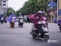 """中国天气网广西站讯 在台风""""圆规""""的外围云系和冷空气的共同影响下,今天(10月13日)早上,钦州市城区出现偏北8级阵风,市民顶风出行。(图文/李斌喜)"""