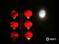 """中国天气网讯   中秋佳节夜,月圆人更圆。应是良辰美景,奈何天公不作美,今年的八月十五,河北全省大部分地区难见月色,不过在北部的承德市,晴间多云的夜空让月亮时隐时现,当地市民还欣赏到了""""彩云遮月""""的景观。图为月亮与路边火红的灯笼相映成趣。"""