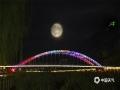 """中秋佳节夜,月圆人更圆。应是良辰美景,奈何天公不作美,今年的八月十五,河北全省大部分地区难见月色,不过在北部的承德市,晴间多云的夜空让月亮时隐时现,当地市民还欣赏到了""""彩云遮月""""的景观。图为一轮明月高高的悬挂在承德武烈河上。"""