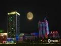 """中秋佳节夜,月圆人更圆。应是良辰美景,奈何天公不作美,今年的八月十五,河北全省大部分地区难见月色,不过在北部的承德市,晴间多云的夜空让月亮时隐时现,当地市民还欣赏到了""""彩云遮月""""的景观。图为月亮与城市建筑的霓虹灯共同构成美丽的风景。"""